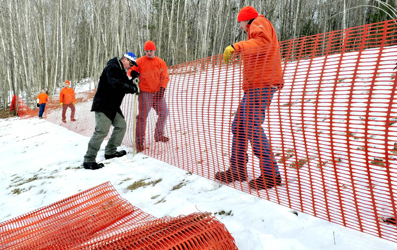 Steven Buzzell, center, of the Waterville parks and recreation department, works with Kennebec County jail inmates Joey Johnson, right, and Shawn Peaslee on a fence for the sledding hill at the Quarry Road Recreation Area in Waterville on Monday. The Winter Carnival runs Saturday from 10 a.m. to 2 p.m. and features sledding, snowshoe races, ski instruction, a bonfire, food and the Amazing Tree Maze.