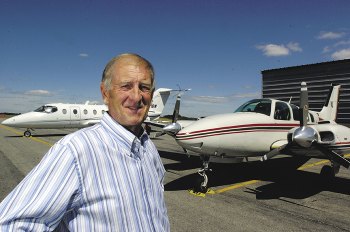 Bill Perry, owner of Maine Instrument Flight at the Augusta State Airport, with a prop plane and a jet.