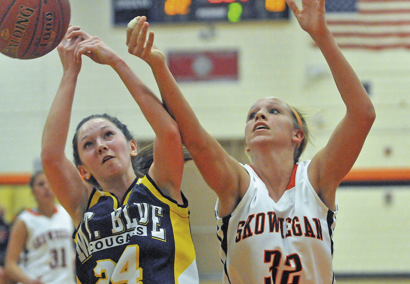 Mt. Blue High School's Amy Hilton, 24, left, and Skowhegan Area High School's Morgan Buker, 32, right, battle for the rebound in the first half in Skowhegan Friday..