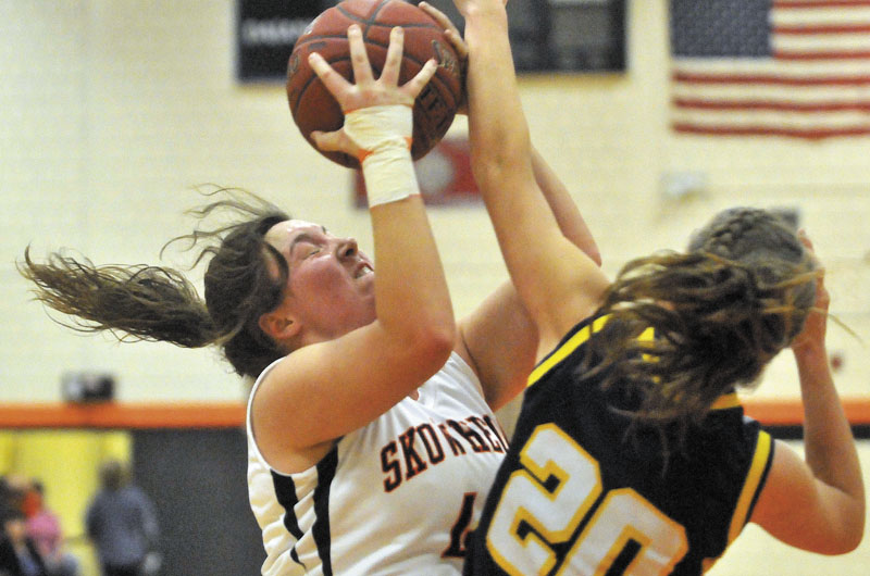 Skowhegan Area High School's Andrea Quirion, 44, left, battles for the rebound with Mt. Blue High School's Mackenzie Conlogue, 20, right, in the first half in Skowhegan Friday.