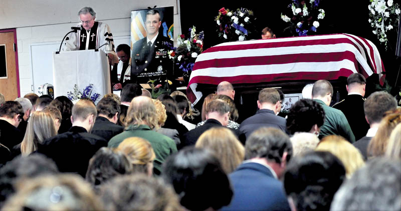 The Rev. David Smith leads a prayer during a funeral service on Sunday for Lt. Col. Michael Backus, 44, of Wilton, who died unexpectedly on Jan. 7 at Camp Keyes in Augusta. The service was held at the University of Maine in Farmington before an overflow crowd of family, friends and service members.
