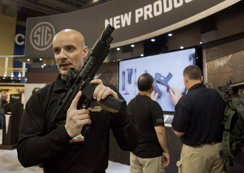 "Adam Painchaud of Sig Sauer explains one of the company's newest products, the MPX 9mm pistol caliber submachine gun, at the 35th annual ""SHOT show"" Tuesday in Las Vegas. The gun is for military and law enforcement use and not for sale to the public."