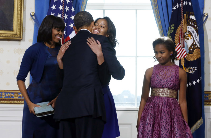 President Obama hugs daughter Malia as first lady Michelle Obama and daughter Sasha watch after Obama was officially sworn into office by Chief Justice John Roberts, not pictured, in the Blue Room of the White House on Sunday.