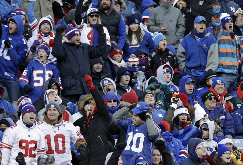 BUNDLE UP: New York Giants fans cheer during a game on Dec. 30, 2012 in East Rutherford, N.J. Just over a year before the New York area hosts the Super Bowl, the temperature was in the teens. With an outdoor game in a cold-weather state, the NFL will be at the mercy of Mother Nature for the 2014 championship.