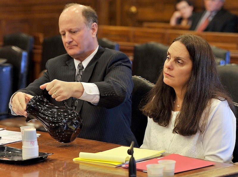 William Childs, attorney for Paula Spencer, pours a glass of water as she listens to the judge give instructions to the attorneys before opening arguments.