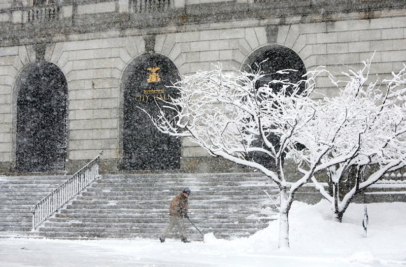 Pat Farrell, an employee of the Portland Recreation and Facilities Department, shovels the front of City Hall during the heavy snow Sunday in Portland. By noon Farrell and his co-workers had shoveled at City Hall four times.