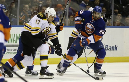 Boston Bruins left wing Milan Lucic (17) controls the puck in front of New York Islanders left wing Matt Moulson (26) in the first period of their NHL hockey game at Nassau Coliseum in Uniondale, N.Y., Tuesday, Feb. 26, 2013. (AP Photo/Kathy Willens)