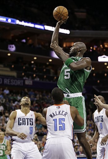 Boston Celtics' Kevin Garnett (5) shoots over Charlotte Bobcats' Kemba Walker (15) and Gerald Henderson (9) during the second half of an NBA basketball game in Charlotte, N.C., Monday, Feb. 11, 2013. The Bobcats won 94-91.
