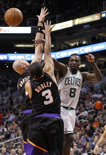 Boston Celtics forward Jeff Green, right, passes the ball off as he is double-teamed by Phoenix Suns center Marcin Gortat, left, of Poland, and Jared Dudley, center, in the first half of an NBA basketball game Friday, Feb. 22, 2013, in Phoenix. The Celtics won 113-88.(AP Photo/Paul Connors)