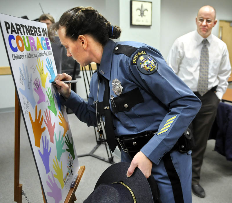 Maine State Police Lt. Anna Love signs the board for the Children's Advocacy Center with Kennebec County Sheriff's Det. Sgt. Frank Hatch, right, Monday during a ceremony in Augusta to the mark the center's new interagency agreement to provide sexually abused children streamlined access to investigators and social services in Kennebec and Somerset Counties.