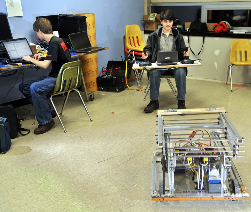 Gardiner Area High School robotics team member Ian Basford, right, steer his team's robot Thursday with dual joysticks, while teammate Harris Plaisted checks the code for the remotely operated machine on a computer.