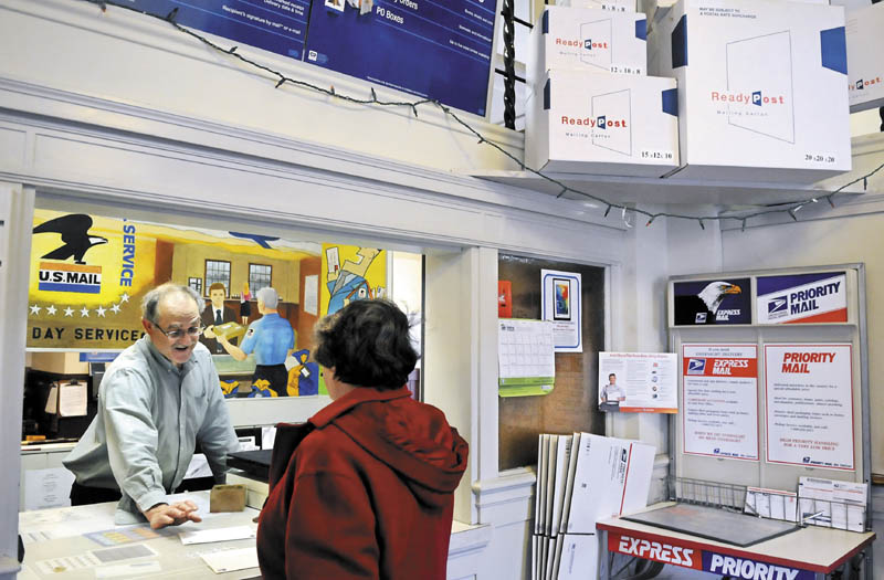 Hallowell Post Master Ed Boutin assists customer Joan Haig Wednesday at the counter. The US Postal Service is ending Saturday letter delivery in August.