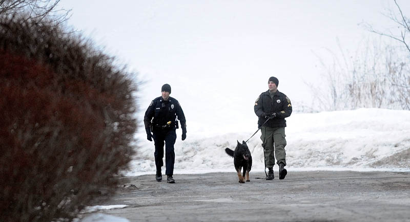 A Waterville police officer, left, and Kennebec County Sheriff K-9 unit search the closed dirt access road that connects the doctor's complex at 325 Kennedy Memorial Drive with Lincoln Street for a man who robbed Key Bank on Kennedy Memorial Drive Thursday afternoon.