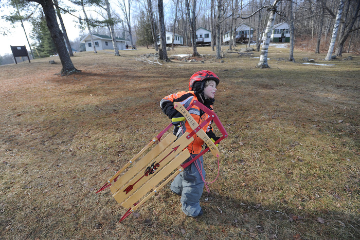 Mario Wilbur, 7, of East Madison, lugs his Flexible Flyer across the grassy hill en route to the ice fishing derby at Lake George, on the Skowhegan and Canaan town line, on Saturday. Wilbur said that even though there is no snow, the sled works perfectly fine on the frozen lake.