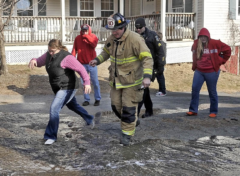 Kimberly Guite, 46, left, leaps over a pool of water in her socks with the help of Waterville Fire department Lt. Scott Holst, on Squire Street in Waterville Thursday. Guite lost her rental home to fire. Guite narrowly escaped a fire that broke out in her home. She didn't have time to put her shoes on.