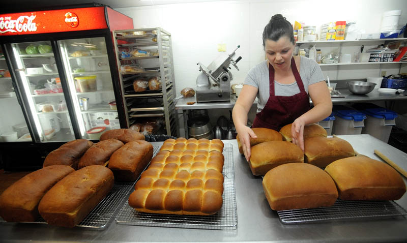 Heather Beane pulls some fresh-baked bread out of the oven, and places the loaves on cooling racks, at Thompson's Restaurant on Main Street in Bingham on Wednesday.