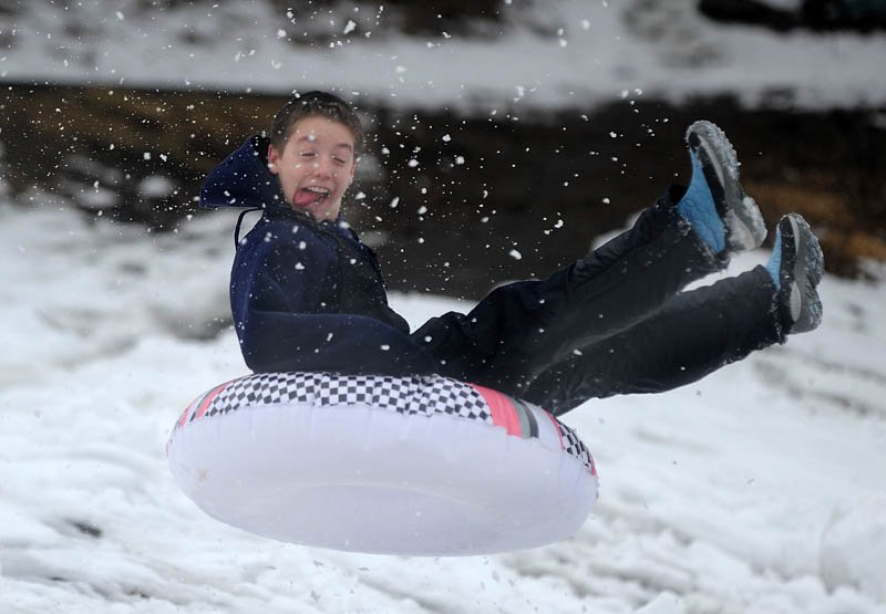 Anthony Visconti, 13, of Waterville, launches off a jump at the Sherwin Street hill in Waterville Wednesday. The storm closed schools early Wednesday affording area kids the opportunity to sled one more time on the icy hill before fresh snow slows down the descent.