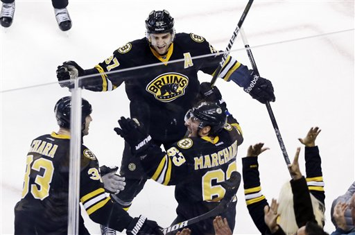Boston Bruins left wing Brad Marchand (63) celebrates with defenseman Zdeno Chara (33) and center Patrice Bergeron (37) after his goal tied them with the New York Rangers near the end of the third period of an NHL hockey game in Boston, Tuesday, Feb. 12, 2013. (AP Photo/Elise Amendola)