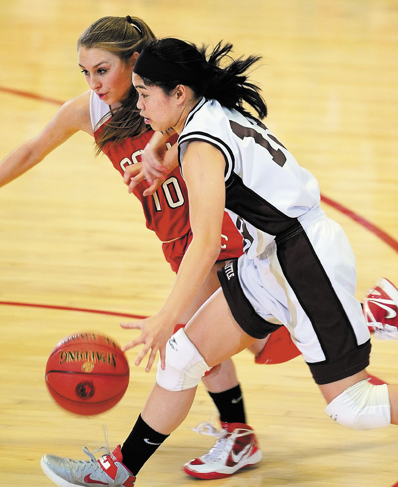Cony's Olivia Deeves, left, tries to stop drive by Edward Little's Katherine Sawyer during an Eastern Class A tournament game on Friday February 15, 2013 at the Augusta Civic Center.
