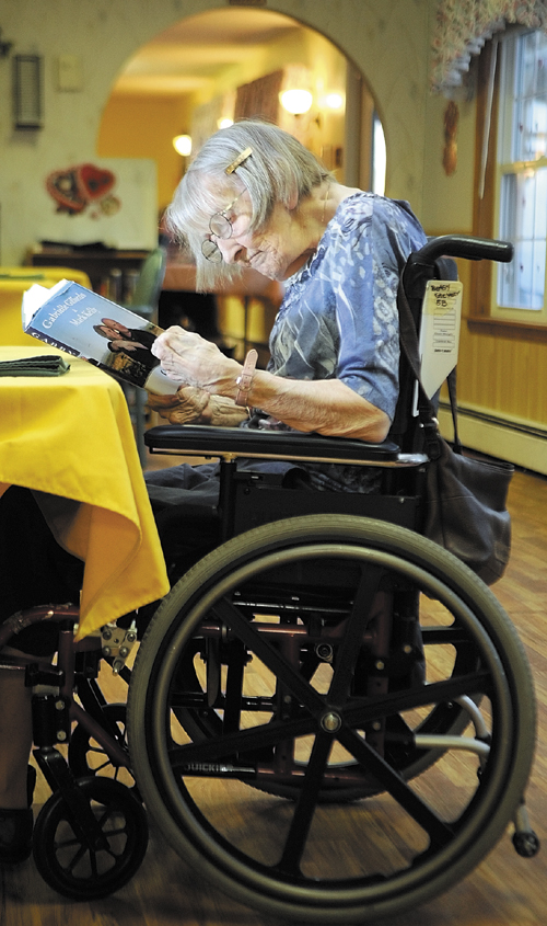 Betsy Stevens reads a book in the dining room on Friday at Heritage Rehabilitation & Nursing Center in Winthrop.