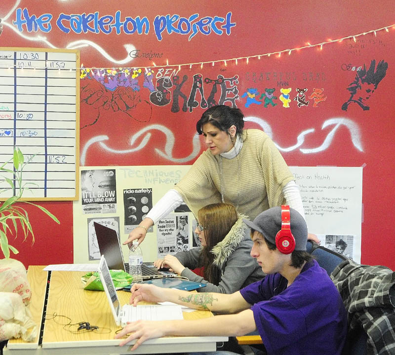 Teacher Evelyne Walther, standing, works with Liz Kenney, of Monmouth, as Anthony Ridley, of Monmouth, works on his own on Wednesday, at the Carleton Project building in Winthrop.