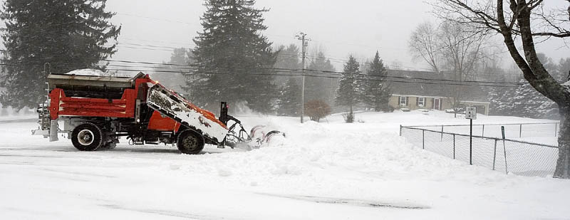 Augusta Public Works plow truck driver Stan Moore makes several passes as he clears the intersection of Leighton and Mount Vernon Roads around 10:45 a.m.. on Saturday, cleaning up from the blizzard in Augusta.