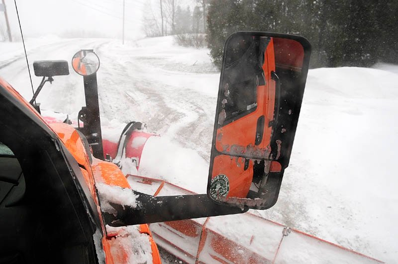 Snow flies of the plows of the truck driven by Augusta Public Works plow truck driver Stan Moore on Saturday.