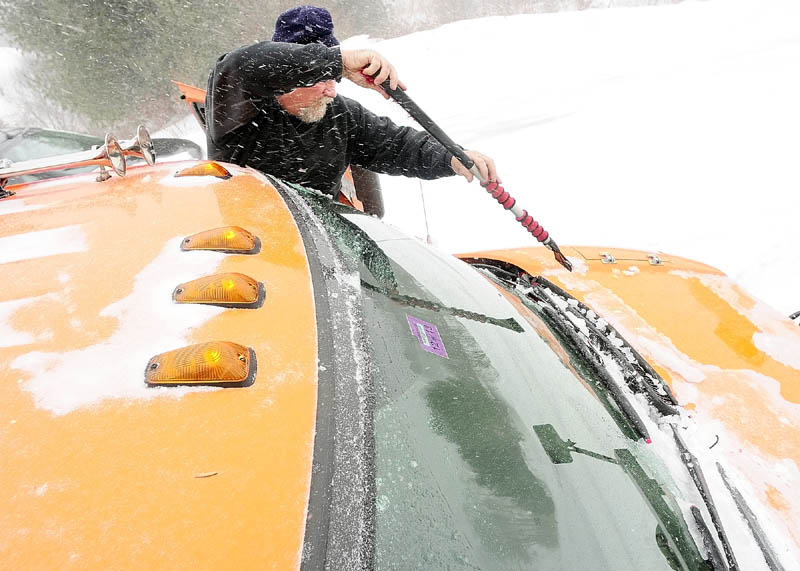Augusta Public Works plow truck driver Stan Moore scrapes ice off the windshield while plowing rural roads on Saturday.