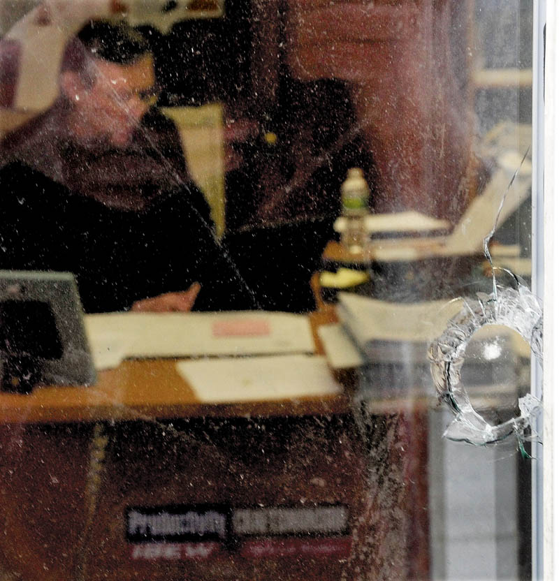 A hole from a BB gun is seen in one of five windows damaged at the International Brotherhood of Electrical Workers Local 1253 office in Fairfield, as Training Director Christopher Trider works inside on Monday.