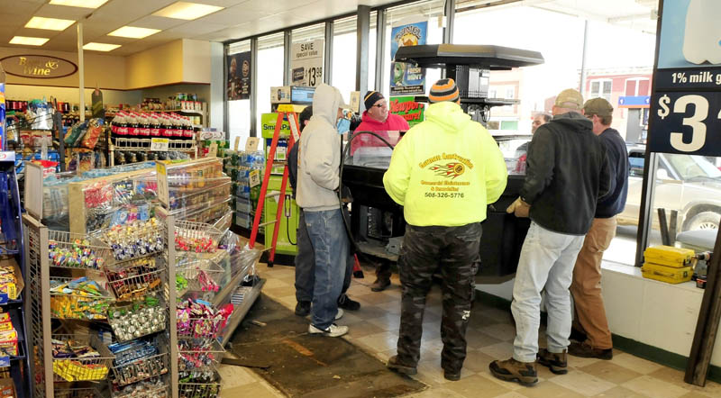Workers with Gorman Construction carry a food case through the storefront windows which were removed at Cumberland Farms in Fairfield, on Monday. The store is expanding and offering a larger coffee and sandwich counter.
