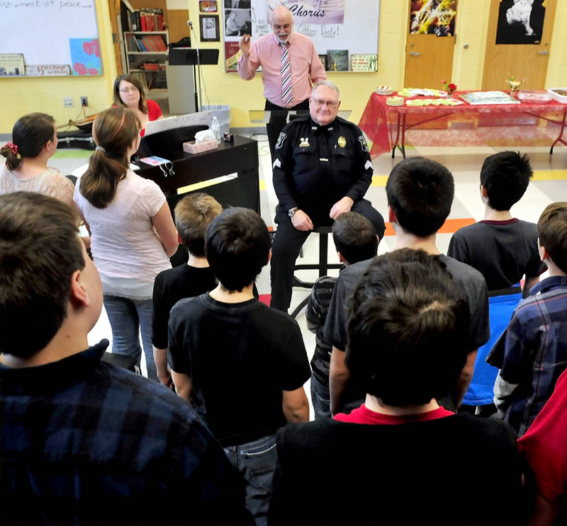 School Resource Officer Dusty Woodside, seated, was surprised by 75 seventh and eighth grade students at Messalonskee Middle School in Oakland who sang Valentine's Day songs in honor of his many years involved in schools. Woodside is retiring this summer. Behind Woodside are co-Chorus Directors Pamela and Kevin Rhein.