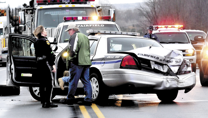 Fairfield police officer Shana Blodgett and Det. Sgt. Kingston Paul confer outside the cruiser that was destroyed, injuring officer Bill Beaulieu after the cruiser and a tractor trailer truck collided on U.S. Route 201 in Fairfield on Thursday, Jan. 31. The roadway was closed for hours as police from several departments investigated the accident.