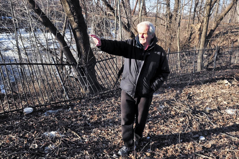 Jack Nivison speaks from a wooded area beside the Kennebec River, on the Winslow side of the Ticonic Bridge, where crews have cleared debris on Tuesday. The site is near where a barber shop, drug store and photography shop once stood.