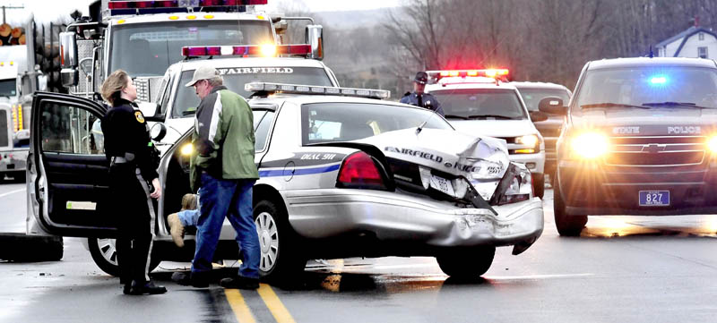 Fairfield police officer Shana Blodgett and Detective Sgt. Kingston Paul confer outside the cruiser that was destroyed, injuring officer Bill Beaulieu, after the cruiser and a truck collided on U.S. Route 201 in Fairfield on Thursday.