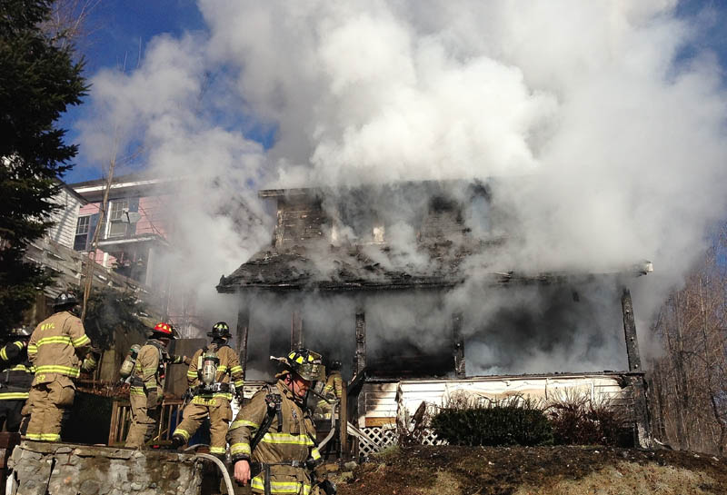 Firefighters battle a house fire on Squire Street in Waterville Thursday morning.