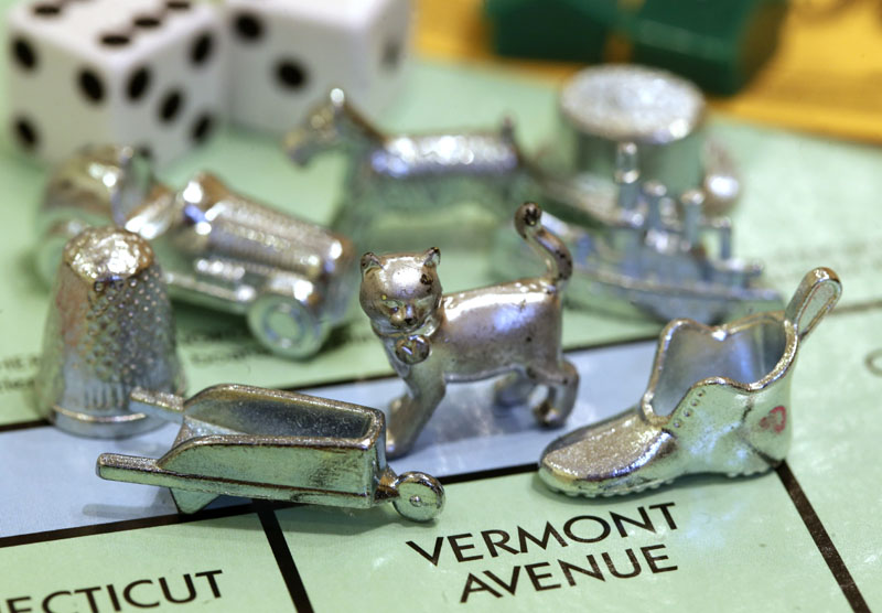 The newest Monopoly token, a cat, center, rests on a Boardwalk deed next to other tokens still in use including the wheelbarrow, left, and the shoe, right, at Hasbro Inc. headquarters, in Pawtucket, R.I.. Voting on Facebook determined that the cat would replace the iron token.