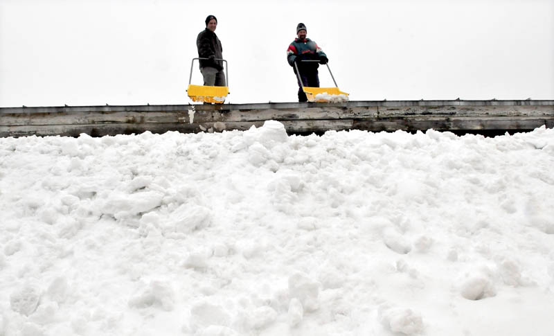 The falling rain added weight to the roof of Madison Mattress and Furniture store on Thursday, so Andy Deuble, left, and Kevin McLain shoveled off the heavy load.