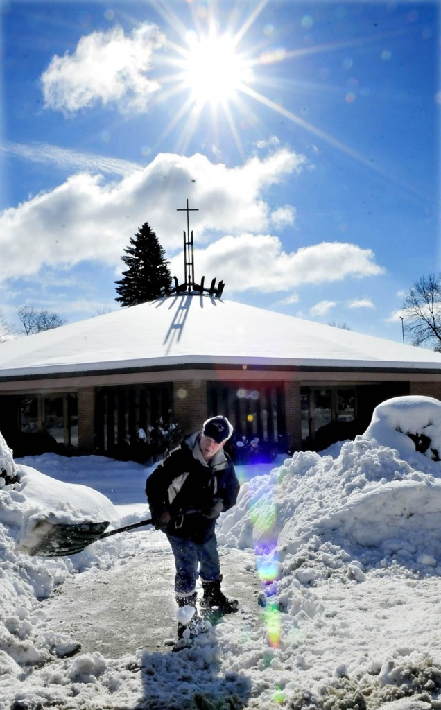 BLESS THIS MESS: Reggie Vashon shovels snow in the shadow of the sun and cross on the roof of Notre Dame Catholic Church in Waterville on Monday, Feb. 25, 2013.
