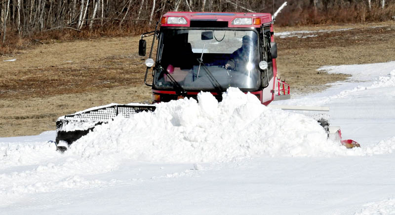 Sam Green of the Waterville Parks and Recreation department uses a snow groomer to move piles of snow made at night by snow-making machines at the Quarry Road Recreation Area on Tuesday.