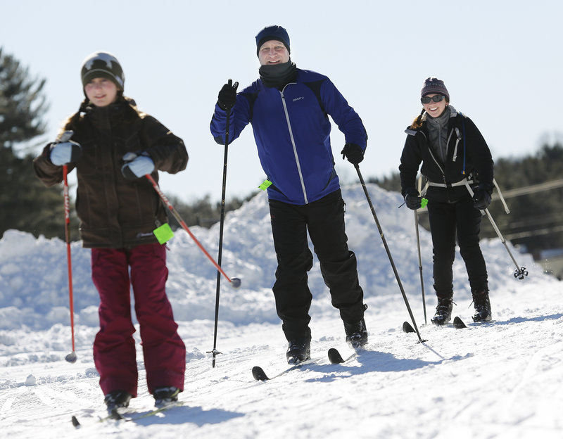 Scott Forrey of Cape Elizabeth skis Sunday with his wife, Patrice, and daughter Haley, 10, at Pineland Farms in New Gloucester, where a variety of winter activities were free for veterans and their families.