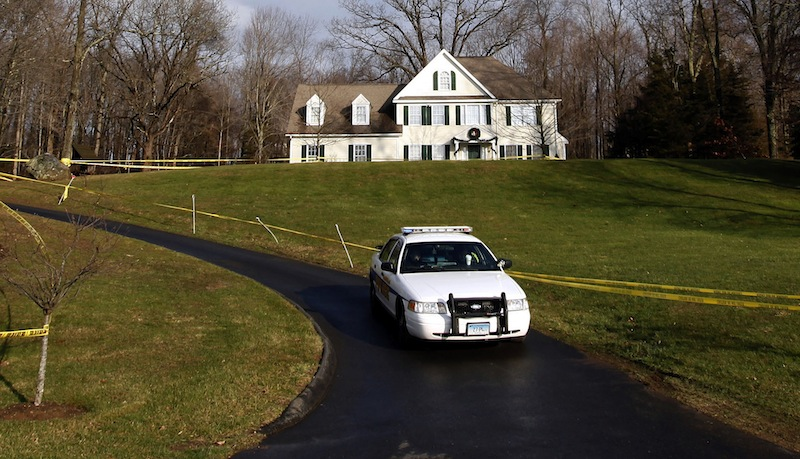 In this Dec. 18, 2012 file photo, a police cruiser sits in the driveway and crime scene tape surrounds the home of Nancy Lanza in Newtown, Conn. Nancy Lanza was killed in the home by her son Adam Lanza before he forced his way into Sandy Hook Elementary School in Newtown, Conn, killing 26 people. Search warrants released Thursday, March 28, 2013, revealed that an arsenal of weapons including guns, more than a thousand rounds of ammunition, a bayonet and several swords was seized in the Lanza home. (AP Photo/Jason DeCrow)