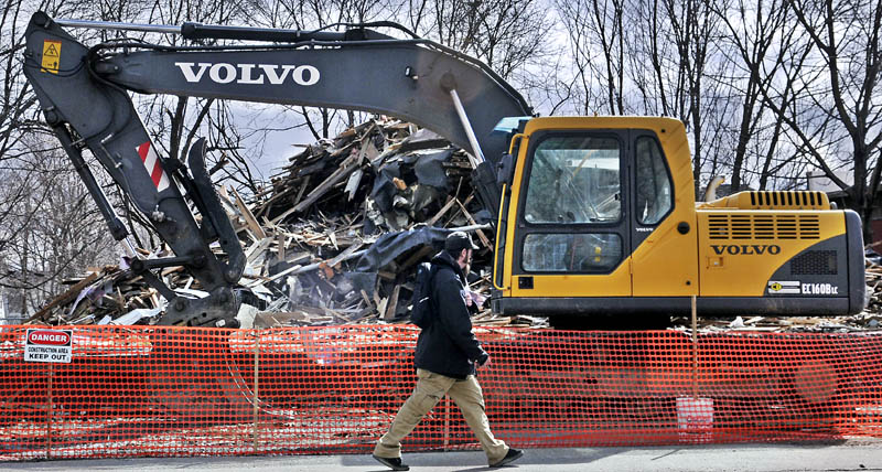 An excavator sits next to the debris from an apartment building that was razed over the weekend at 55 Sewall St. in in Augusta Monday. The four-story building was destroyed by fire Jan. 10.