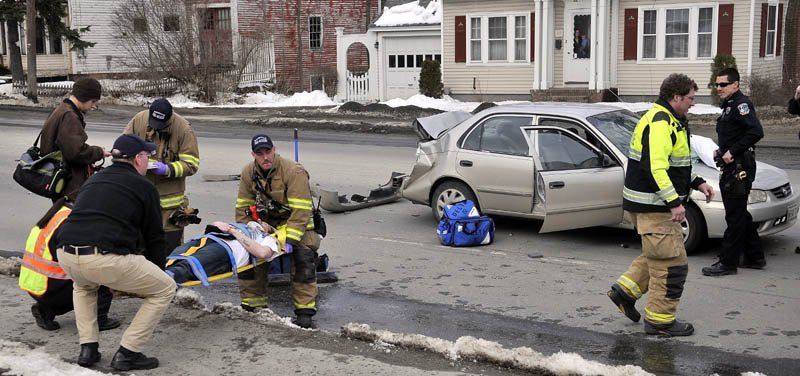 Rescue workers from the Waterville fire department, Delta Ambulance and Waterville police department tend to people injured in an accident on Upper Main Street Friday afternoon.