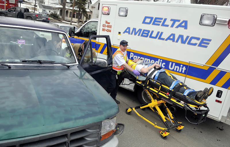 A Delta Ambulance emergency medical technician transports a victim of a two-car accident to a waiting ambulance, as a Waterville firefighter talks to Albert DiPietro, 28, of Richmond, seated in his truck, on Upper Main Street Friday afternoon. DiPietro's truck struck the rear end of a car, sending two adults and two children to MaineGeneral Medical Center's Thayer Campus for neck and back pain and minor injuries.