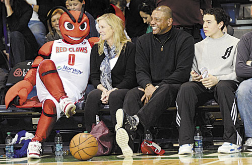 FAMILY TIME: Boston Celtics coach Doc Rivers, his wife Kristen, left, and youngest son Spencer, right were at the Portland Expo to watch his son, Jeremiah, play with Red Claws when Crusher sat beside the family during a break in the action Sunday.