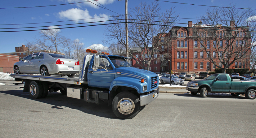 A flatbed tow truck pulls away Tuesday morning from Parish Place Apartments in Biddeford with a silver Chevy Malibu with Massachusetts plates. Residents say it was the car in which a man's body was found this morning.