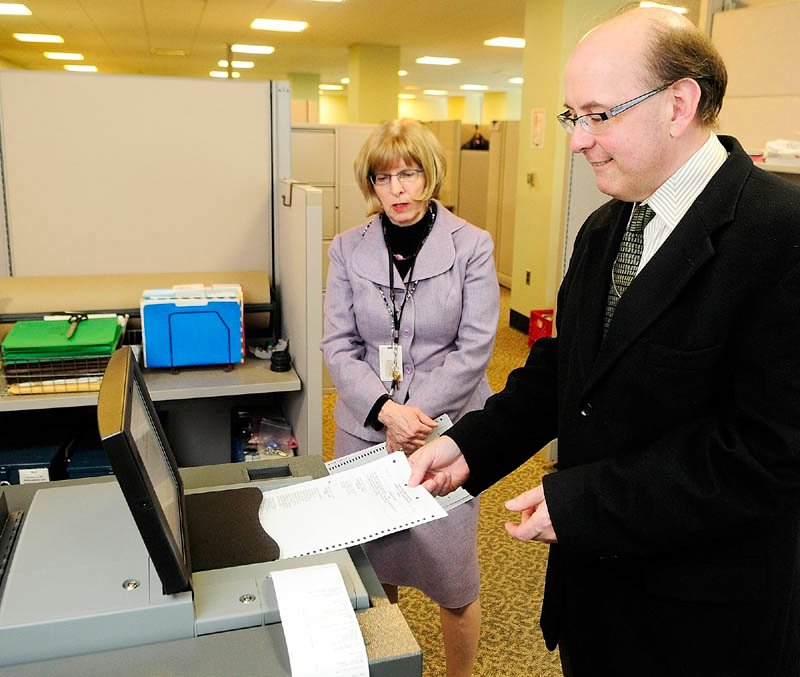 Deputy Secretary of State Julie Flynn, left, and Secretary of State Matt Dunlap give a demonstration of one of the the new, state-leased DS 200 tabulators on Thursday in the Cross Building in Augusta. Litchfield recently rejected a second offer by the state for a machine to tabulate state and federal election ballots, in favor of continuing hand-counting.