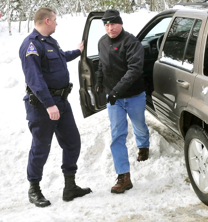 Bob Joy, father of missing skier Nicholas Joy, arrives at the site where his son was brought out by snowmobile Tuesday morning. At left is Carrabassett Valley police officer Randy Walker.