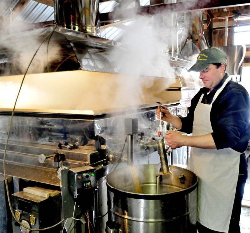 Jeremy Steeves uses a hydrometer to check the sugar density of maple syrup coming out of an evaporator at Strawberry Hill Farm in Skowhegan on March 11. Steeves and his father, Jack, are making syrup for retail and the Sunday's Maine Maple Sunday event.
