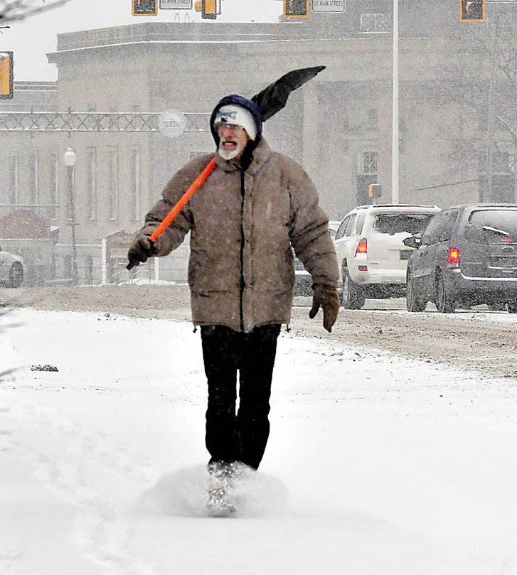 OPPORTUNITY KNOCKS: Ralph Norton gets at least one more day of winter to make money shoveling sidewalks and porches as he and his snow shovel trudge along Main Street in Waterville on a snowy Tuesday. Wednesday is the first day of spring, but forecasts are calling for more snow this week.